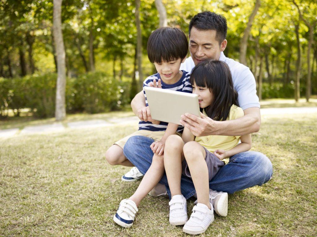 Un Padre y sus hijos con una tablet